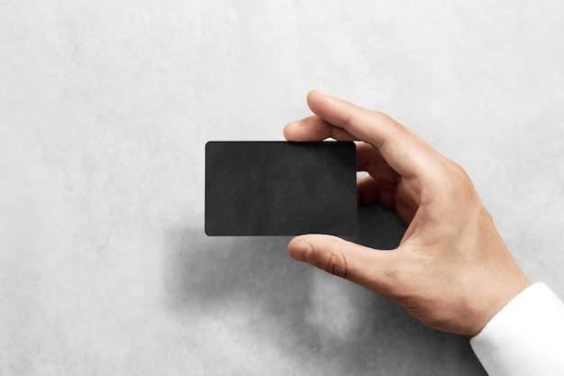 Mão segure o cartão de ofício preto em branco com cantos arredondados