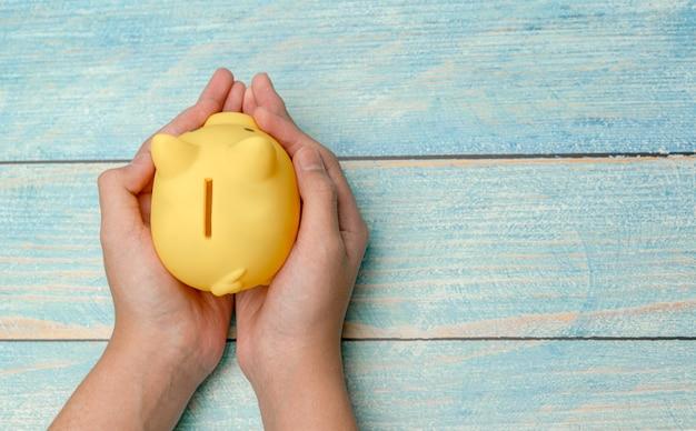 Mão segure o cofrinho para economizar dinheiro em fundo de madeira