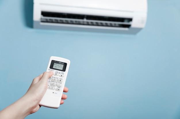 Mão segure o controle remoto do ar condicionado operacional, close-up tiro de mão segurando o controle remoto do branco ar condicionado.