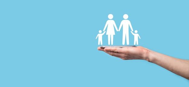 Mão segure o ícone da família jovem. seguro de vida familiar, apoio e serviços, política familiar e conceitos de famílias de apoio. conceito de família feliz. copie o espaço. mãos em concha mostrando a família do homem de papel