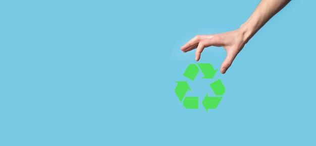 Mão segure o ícone de reciclagem.