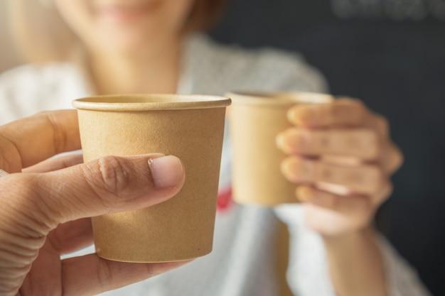 Mão segure o ofício de papel marrom de vidro. mulher segurando um copo juntos