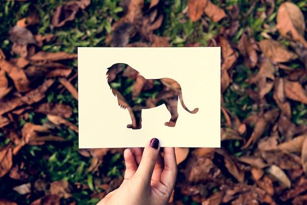 Mão segure o papel de leão escultura com fundo de grama