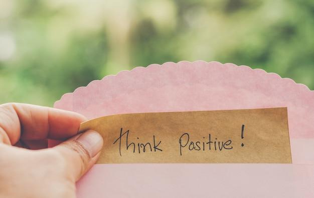 Mão segure pense mensagem positiva em papel pardo