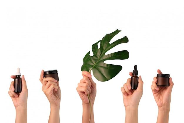 Mão segure skincare cosmético natural sobre fundo branco.