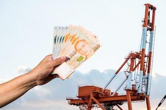 Mão segure um fundo de moeda de Singapura é a carga do porto de contêiner
