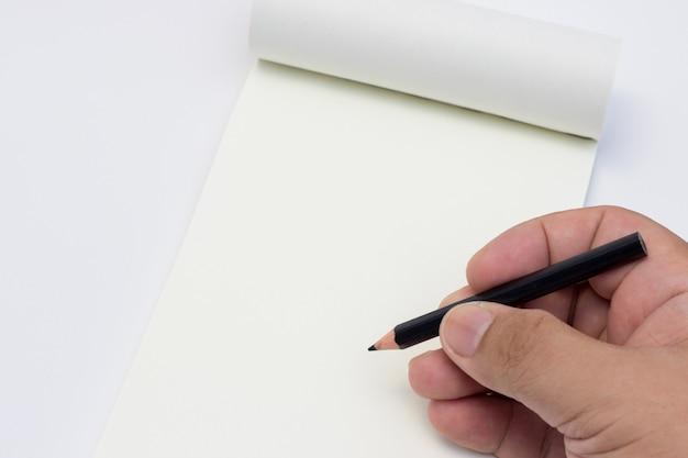 Mão segure um lápis no papel de caderno