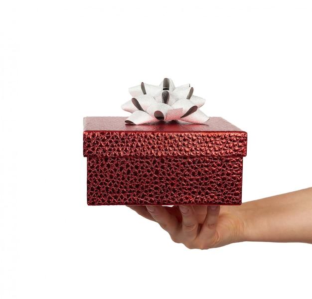 Mão segure um presente embrulhado com laços de seda amarrados, assunto é isolado em um fundo branco