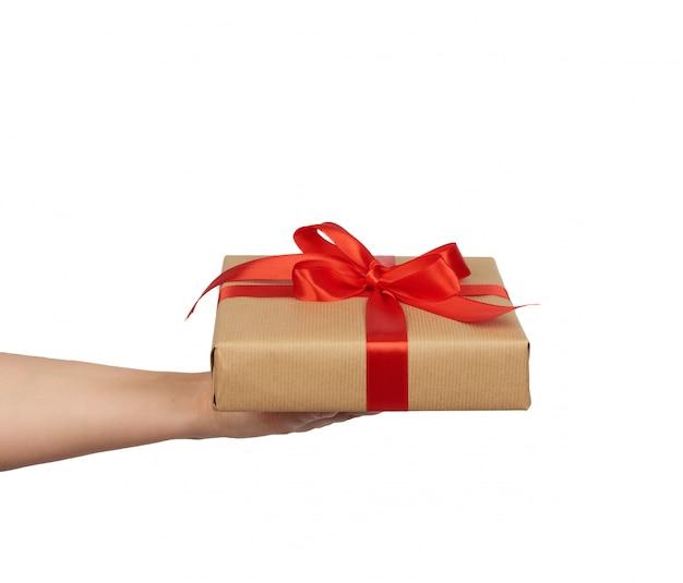 Mão segure um presente embrulhado em papel artesanal marrom com laços de seda amarrados vermelhos, assunto é isolado em um fundo branco