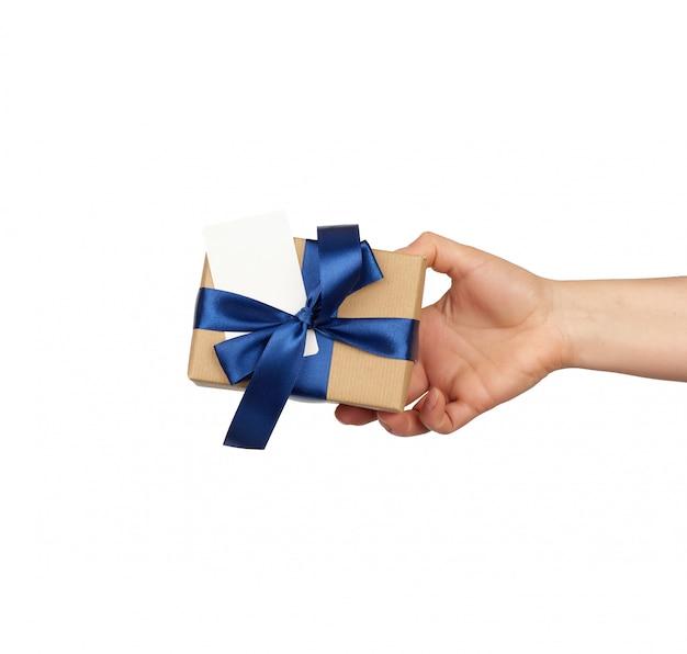 Mão segure um presente embrulhado em papel artesanal marrom com laços de seda azuis amarrados, assunto é isolado