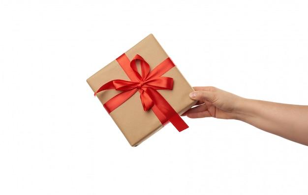 Mão segure um presente embrulhado em papel artesanal marrom com laços vermelhos de seda amarrados