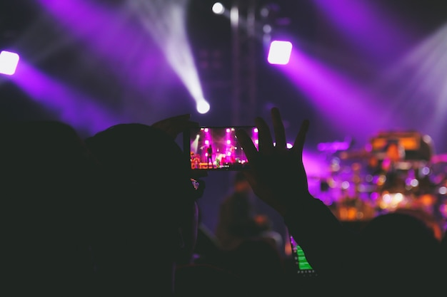 Mão segure um telefone inteligente, tirando foto ou gravando vídeo do palco do concerto