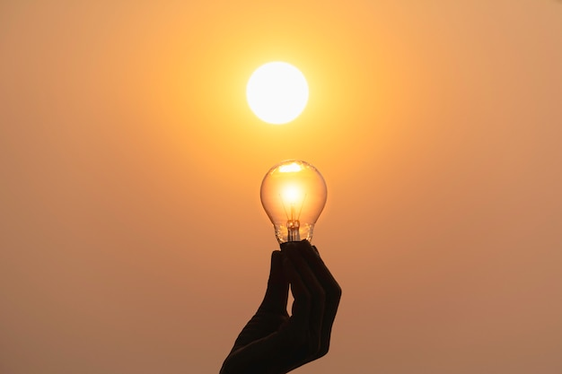 Mão segure uma lâmpada no fundo por do sol para economizar energia
