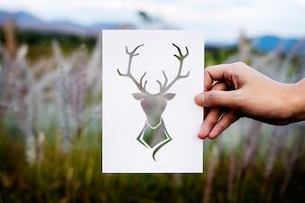 Mão segure veado com chifres, papel, esculpindo, com, natureza