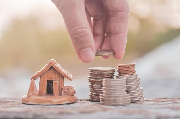 Mão selecionar moedas empilhar modelo de casa na mesa de madeira