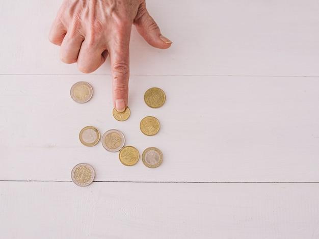 Mão sênior contando moedas de euro na mesa pobreza crise recessão estilo de vida