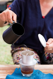 Mão servindo água quente para o café pingar