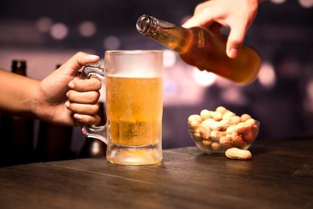 Mão servindo copo de cerveja