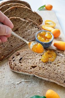 Mão servindo geléia de laranja com uma colher em uma fatia de pão. geléia de kumquat