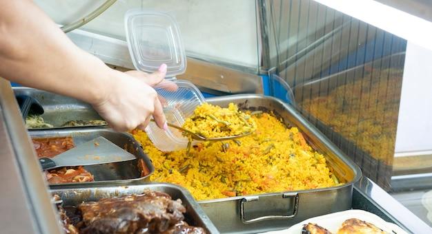Mão servindo uma paella, close-up