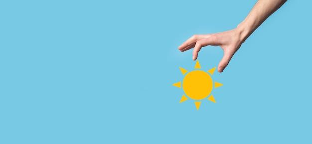 Mão sobre fundo azul contém o símbolo do ícone do sol. fonte sustentável de eletricidade, conceito de fonte de alimentação. abordagem de tecnologia ecologicamente correta.