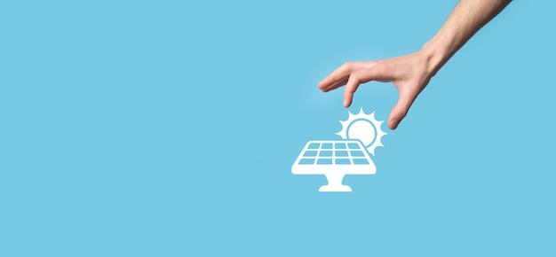 Mão sobre um fundo azul contém o símbolo do ícone de painéis solares. energia renovável, conceito de estação de painéis solares, eletricidade verde.