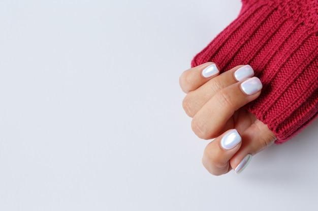 Mão sobre um fundo branco e uma bela manicure