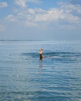 Mão sobressai da água no meio do oceano