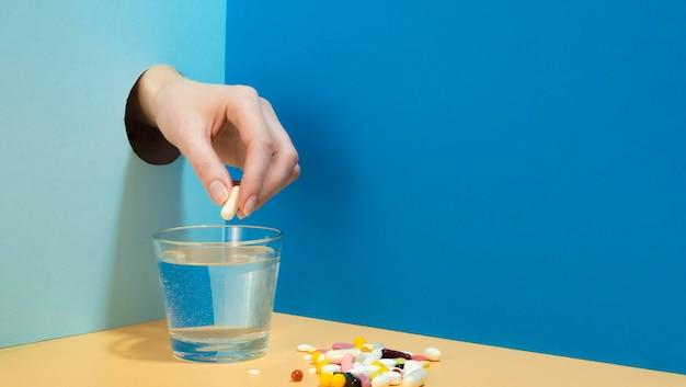 Mão soltando comprimido efervescente em copo de água