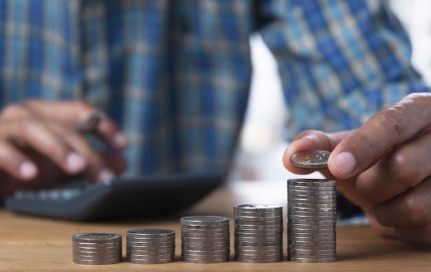 Mão soltar uma moeda com pilha de moedas de dinheiro crescendo para negócios