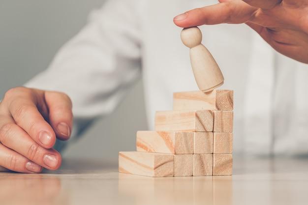 Mão sopra figura abstrata de um homem com uma escada de blocos de madeira