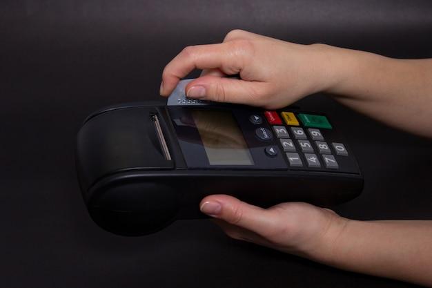Mão swiping cartão de crédito na loja. mãos fêmeas com cartão de crédito e terminal de banco. imagem em cores de um pos e cartões de crédito.