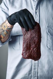 Mão tatuada com luva preta segurando um pedaço de bife luxuoso no ar
