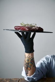 Mão tatuada com luva preta segurando um prato de pedra com bife pronto para cozinhar