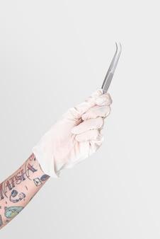 Mão tatuada em uma luva branca segurando uma pinça curva