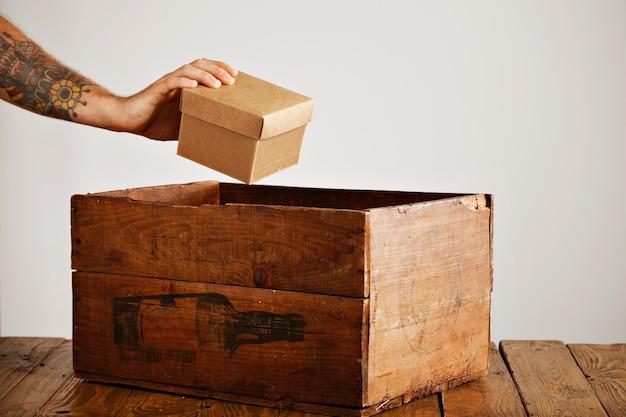 Mão tatuada pega um pacote de papelão de uma velha caixa de madeira na mesa rústica, isolada no branco