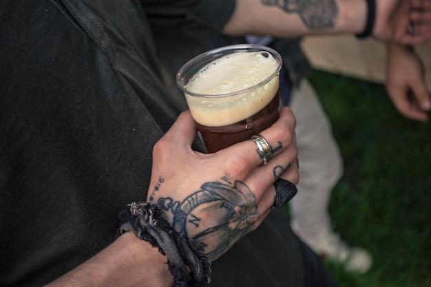 Mão tatuada segurando um copo de cerveja em uma festa