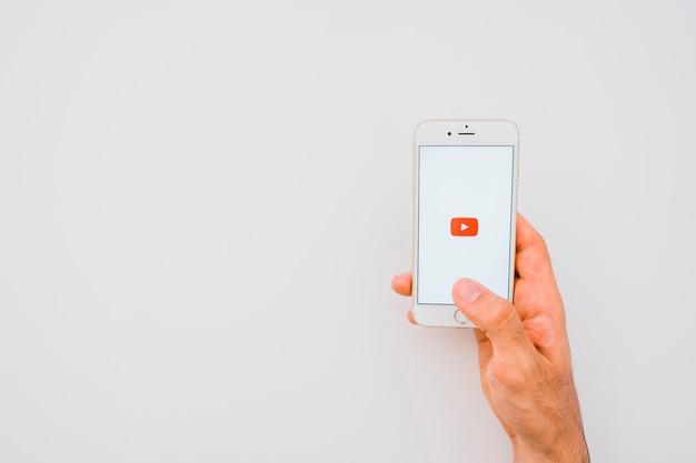 Mão, telefone, aplicativo do youtube e espaço para cópia