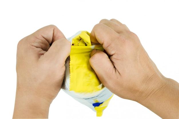 Mão tentando desembrulhar um saco de pastelaria representa o gesto durante uma lágrima do saco usando