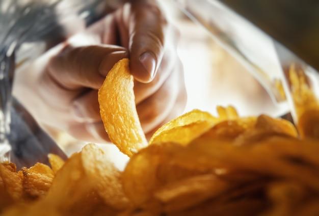 Mão tira batatas fritas dentro da embalagem