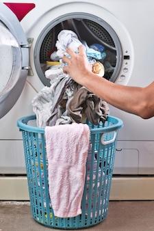 Mão tirando as roupas da máquina de lavar roupa no cesto.