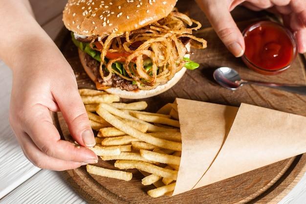 Mão tirando batata frita do pacote de papel na bandeja com hambúrguer