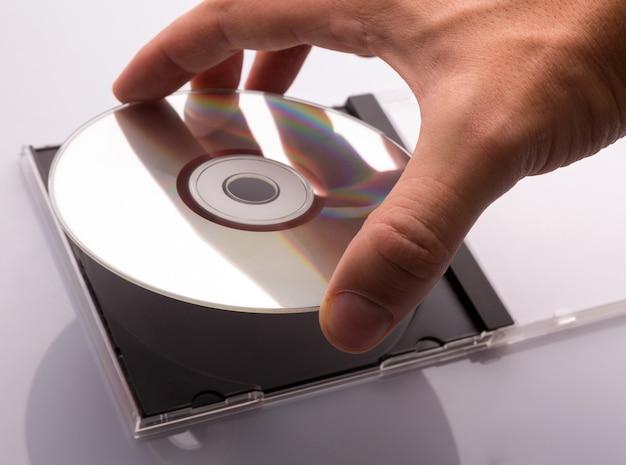 Mão tirando o disco de dvd da caixa.