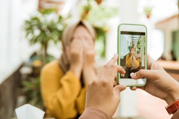 Mão tirando uma foto de uma garota com véu fechar o rosto com a mão usando um smartphone