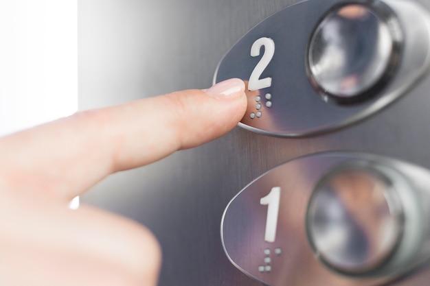 Mão tocando a figura do elevador em braille