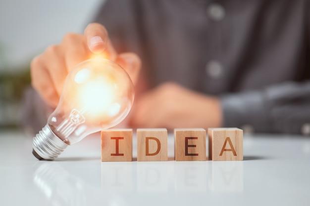 Mão tocando a lâmpada no bloco de madeira com tecnologia inovadora da palavra ideia na ciência