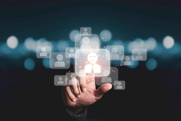Mão tocando a tela virtual do ícone de gestão humana entre o ícone de funcionário para o desenvolvimento humano e o conceito de trabalho em equipe.