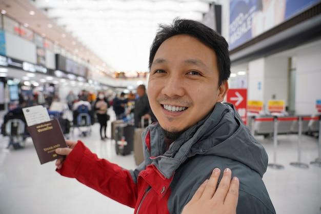 Mão tocando no ombro asiático para cumprimentar o amigo no aeroporto ao esperar o voo a bordo, mão segurando o passaporte com grande bagagem, viajante e amigável