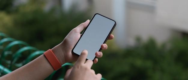 Mão tocando no smartphone de tela em branco em pé na varanda