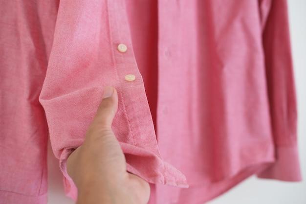 Mão tocando o tecido da camisa